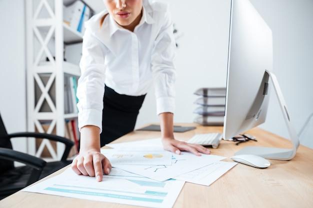 Обрезанное изображение умной серьезной бизнес-леди, указывая пальцем на рабочие документы на столе в офисе