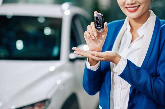 전자 키를 보여주는 웃는 자동차 대리점 관리자의 자른 이미지