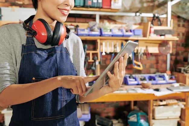 Обрезанное изображение улыбающейся женщины-плотника, проверяющей картинку на планшетном компьютере в поисках вдохновения для создания нового предмета мебели