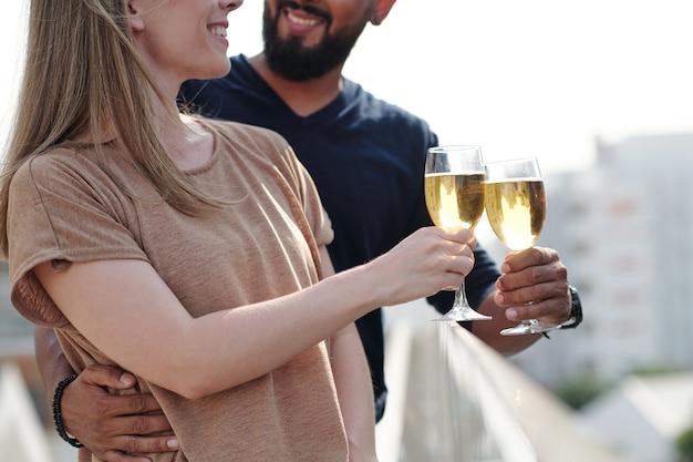 屋上でシャンパンを飲んで楽しんでいる若いカップルを抱きしめて笑顔のトリミング画像