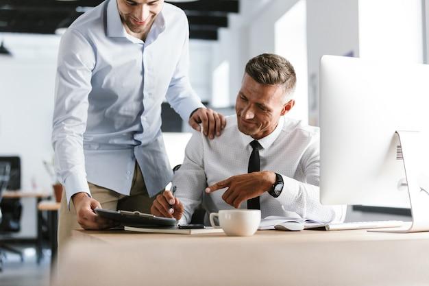 Обрезанное изображение улыбающихся двух коллег, работающих вместе