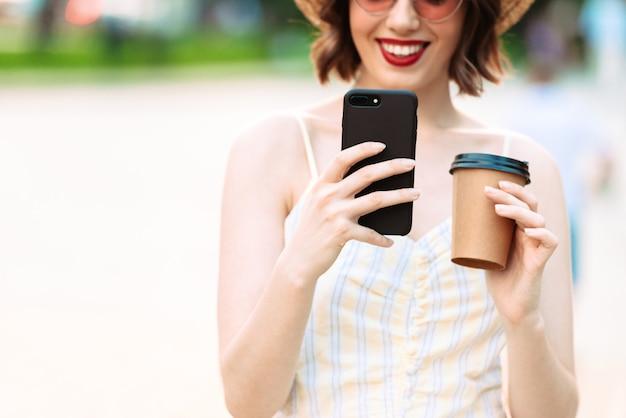 Обрезанное изображение улыбающейся женщины в платье, соломенной шляпе и солнцезащитных очках, использующей смартфон с чашкой кофе в руке на открытом воздухе