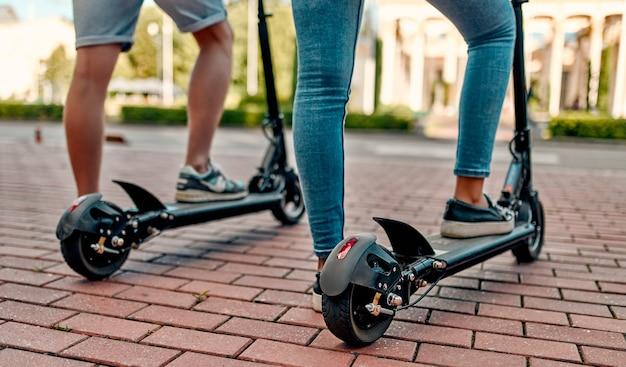 Обрезанное изображение студентов на электросамокатах. парень и девушка на скутерах едут по городской дороге.