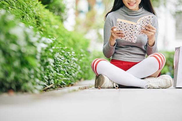 座っているか地面に座って魅惑的な本を読んでいる10代の少女のトリミングされた画像