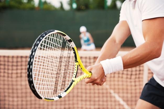 ラケットとコートでテニスの男のトリミング画像