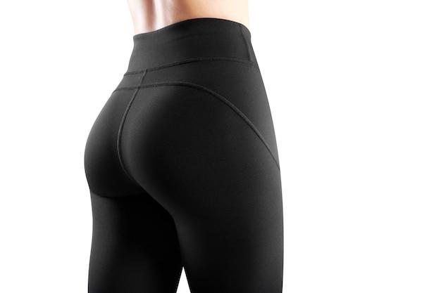 白い背景で隔離のタイトな黒のレギンスに身を包んだ女性モデルの背中のトリミングされた画像。スポーツウェアのコンセプト。水平方向のビュー。