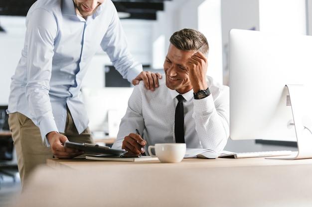 Обрезанное изображение двух счастливых коллег, работающих вместе
