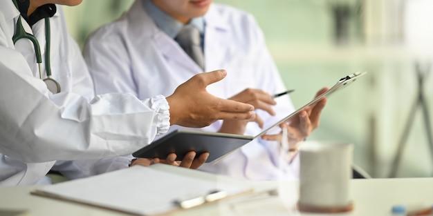 コンピューターのタブレットとクリップボードを保持している医師として働いている2人のスマートな男性の画像を切り取り、議論し、一緒に医師の作業机に規則正しい職場で座っています。