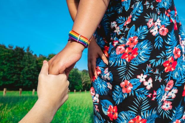 Lgbtプライドを持つ2人の若いアジア人女性のトリミングされた画像、ゲイのレズビアンのペアが手をつないでいます。