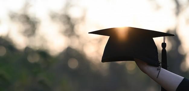 Подрезанное изображение руки студента университета держа шляпу градации в руке сверх outdoors с заходом солнца как предпосылка.