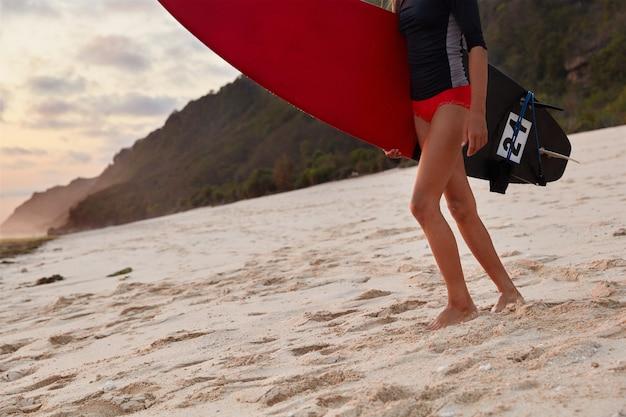 Обрезанное изображение до неузнаваемости подтянутая девушка, одетая в водолазный костюм, держит красную доску для серфинга
