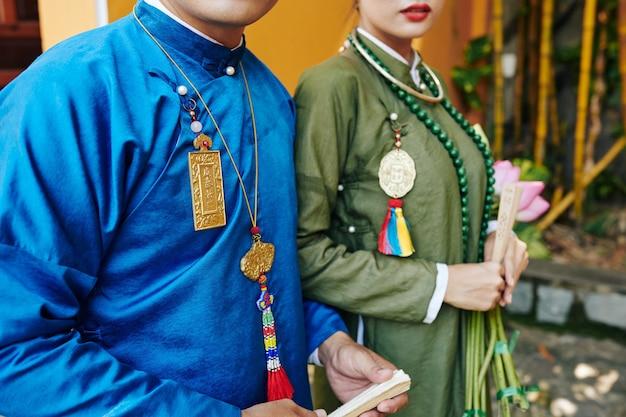 결혼식 후 야외에서 걷는 아오자이 드레스를 입은 베트남 막 결혼한 부부의 자른 이미지