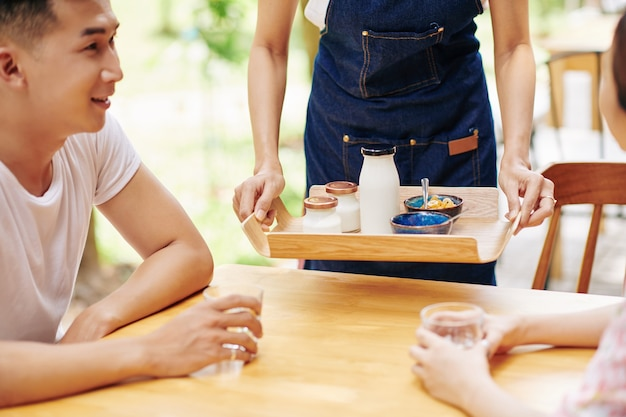 젊은 부부에게 신선한 맛있는 요구르트와 콘플레이크로 구성된 아침 식사를 제공하는 웨이트리스의 자른 이미지