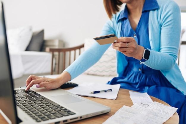 Обрезанное изображение женщины, вводящей информацию со своей кредитной карты при оплате счетов в интернете