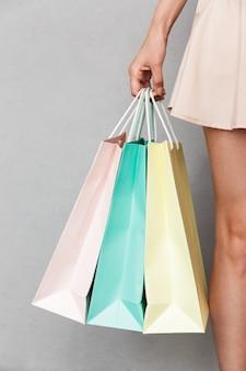 灰色の背景の上に分離された、手に購入品とカラフルな紙の買い物袋を運ぶスカートを着ている女性のファッション買い物客のトリミングされた画像