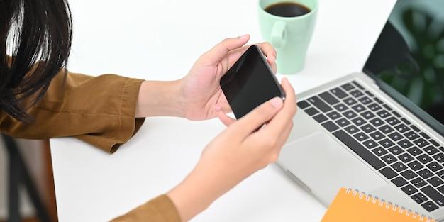 水平に黒い空の画面のスマートフォンを保持している女性のトリミングされた画像。空の画面で携帯電話を使用して映画のコンセプトを見る手。