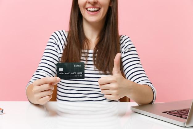 흰색 책상에 앉아 엄지손가락을 보여주는 신용 카드를 들고 평상복을 입은 여성의 자른 이미지