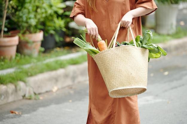 Обрезанное изображение женщины в льняном платье кладет большую морковь в пакет со свежими продуктами, такими как зелень и сельдерей
