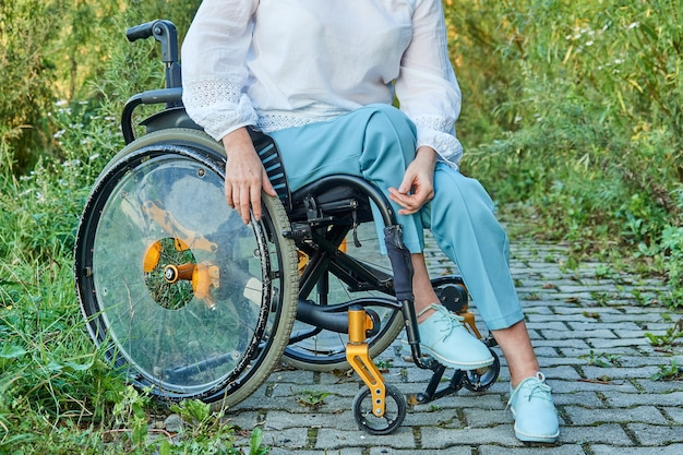 屋外の公園を歩いている車椅子の女性のトリミングされた画像、晴れた秋の天気。