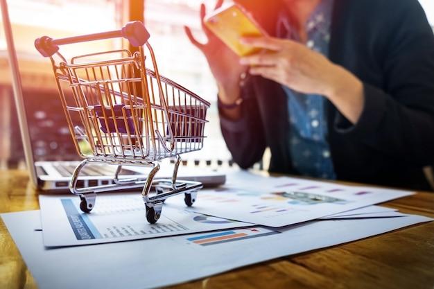 Обрезанное изображение женщины, вводящей карточную информацию и ключ на телефоне или ноутбуке во время покупок в интернете.