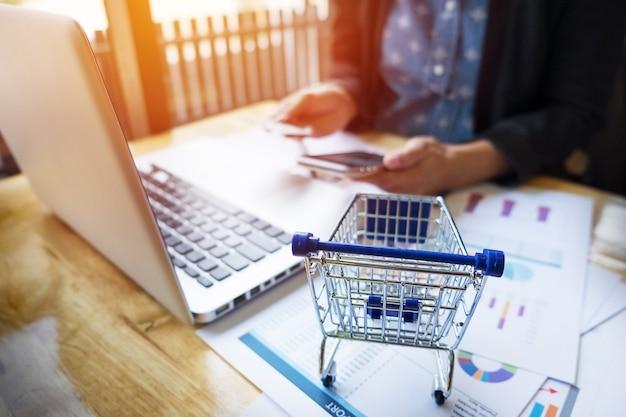 온라인 쇼핑하는 동안 전화 또는 노트북에 카드 정보 및 키를 입력하는 여자의 자른 이미지.