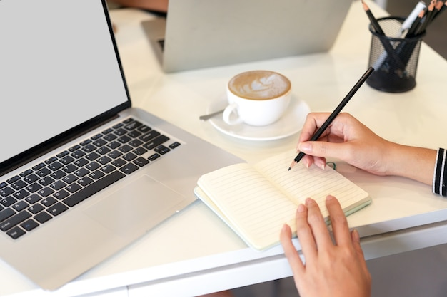 사무실에서 노트북 컴퓨터 모형 커피 머그잔 옆에 있는 노트북에 메모를 하는 여성의 자른 이미지