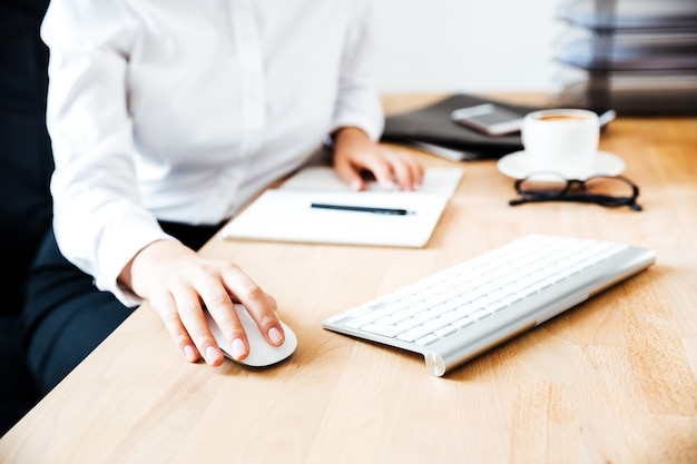 사무실에서 키보드와 마우스를 사용하는 여성 손의 자른 이미지