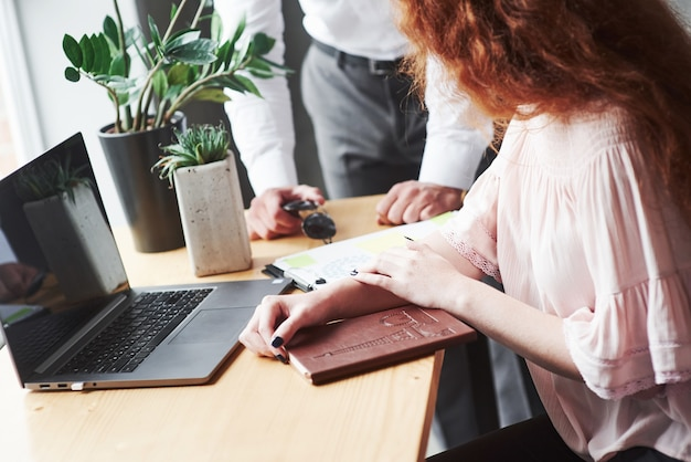 赤毛の女の子と男性、サングラスを保持している職場のトリミングされた画像。