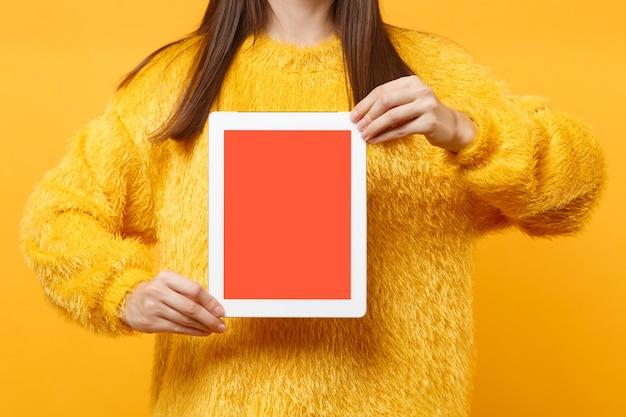 Обрезанное изображение молодой женщины брюнетки в меховом свитере, держащей планшетный компьютер с пустым черным пустым экраном, изолированным на ярко-желтом фоне. концепция образа жизни. скопируйте место для рекламы.