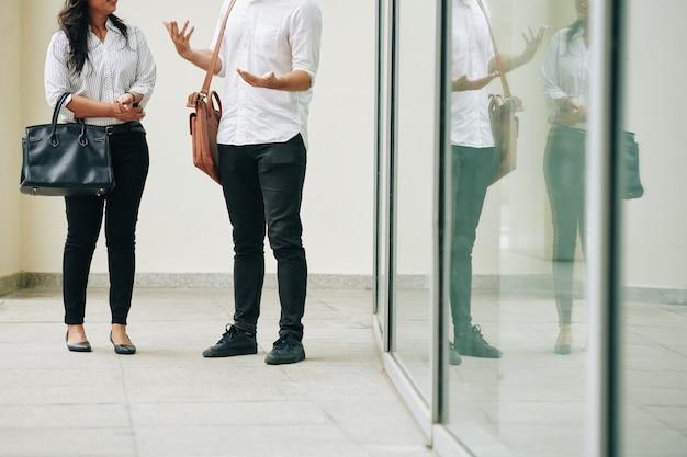 Обрезанное изображение молодых деловых людей, стоящих возле офисного здания и говорящих о важных вопросах