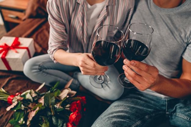 와인, 선물 및 빨간 장미 잔과 함께 침실에서 젊은 부부의 자른 이미지