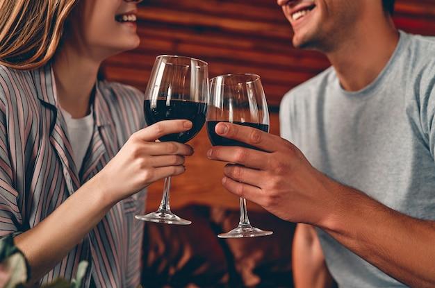 와인 잔과 함께 침실에서 젊은 부부의 자른 이미지