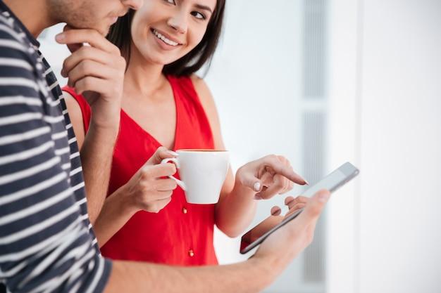 사무실 창문 근처에 태블릿 컴퓨터가 서 있는 젊은 부부의 이미지를 잘랐습니다. 커피 한 잔을 들고 태블릿 컴퓨터를 가리키는 웃는 여자