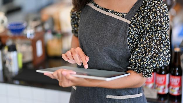 Обрезанное изображение молодой женщины-бариста, принимающей заказ на планшете в кафе
