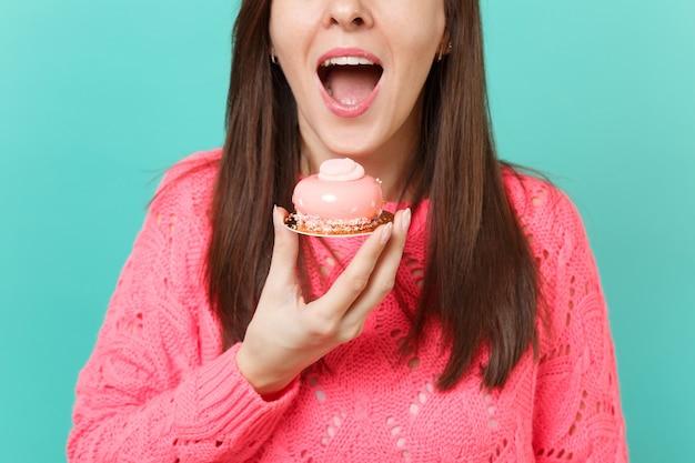 Обрезанное изображение молодой девушки в вязаном розовом свитере, держа в руке, ест торт, изолированные на синем фоне бирюзовой стены студийный портрет. люди искренние эмоции, концепция образа жизни. копируйте пространство для копирования.