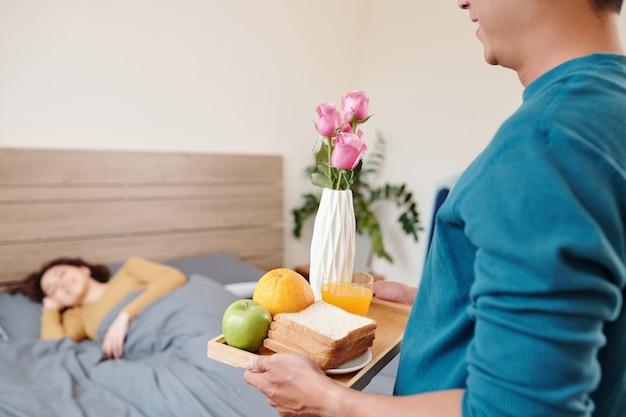 Обрезанное изображение молодого человека, приносящего поднос с тостами, апельсиновым соком, фруктами и цветами, чтобы удивить подругу, спящую в постели