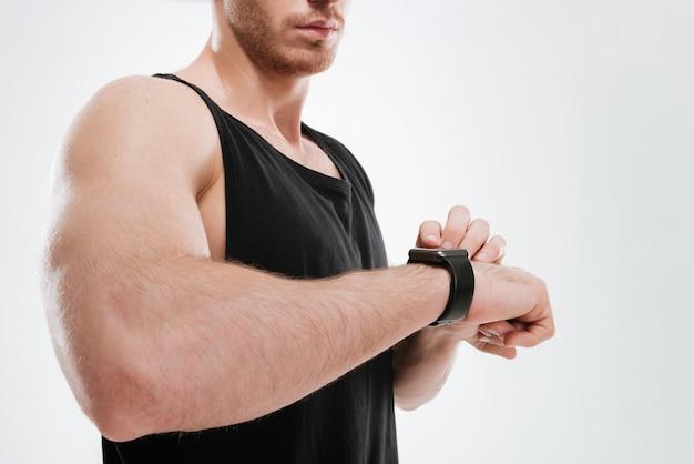 時計を見て白い壁の上に立っている黒いtシャツを着た若い男のトリミングされた画像。