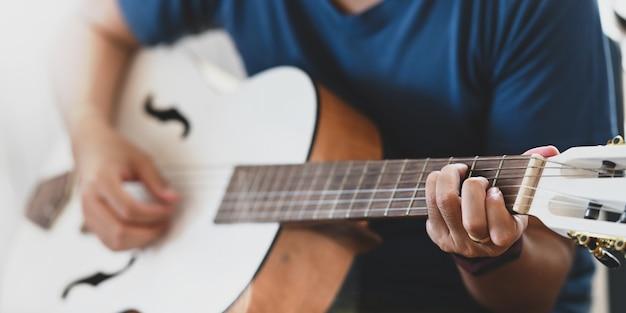 배경으로 거실에 앉아있는 동안 어쿠스틱 기타 연습 젊은 남자의 이미지를 잘립니다. 어쿠스틱 기타 개념을 수행하는 사람.
