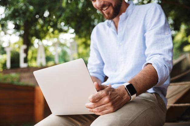 ノートパソコンを使用して若い男のトリミング画像。