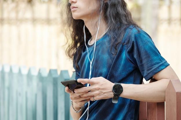 スマートフォンを持って屋外に立って音楽を聴き、目をそらしている若い男のトリミング画像