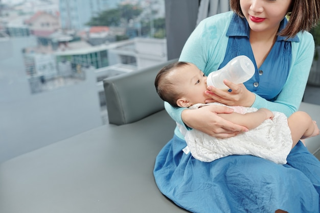 若い母親が幼い娘にミルクを与えている画像のトリミング