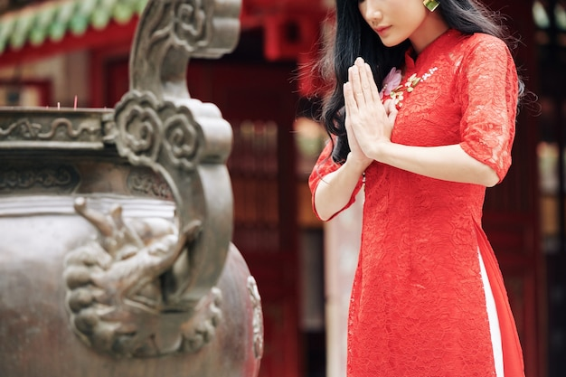 Обрезанное изображение молодой задумчивой женщины в традиционном красном платье, молящейся на открытом воздухе в храме
