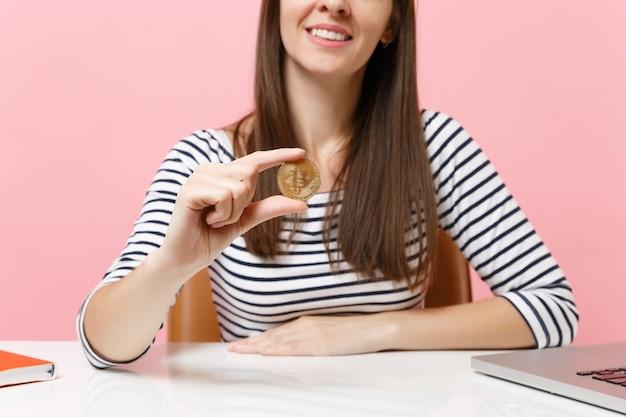 비트코인, 황금색 금속 동전, 미래 화폐가 흰색 책상에 앉아 있는 웃고 있는 젊은 여성의 자른 이미지