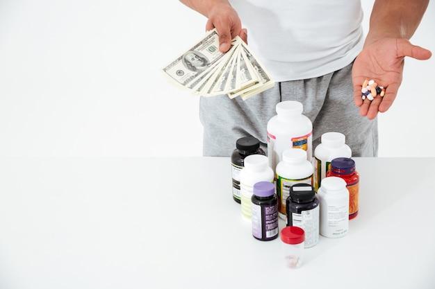 Подрезанное изображение молодого спортсмена держа витамины и деньги.