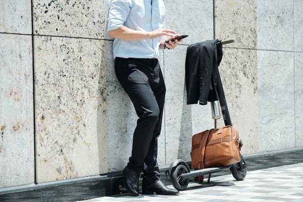 屋外に立って電動スクーターに接続し、スマートフォンでアプリケーションを使用している若いスタイリッシュなビジネスマンのトリミングされた画像