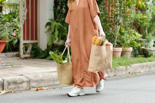 食料品、パン、野菜、果物でいっぱいの2つのバッグを運ぶ若い女性のトリミングされた画像