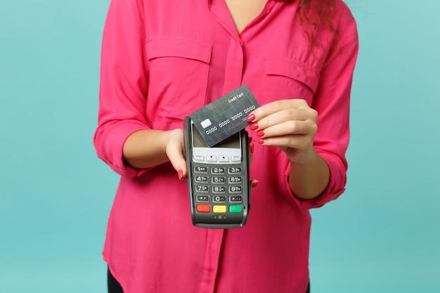 젊은 여성의 자른 이미지는 처리하기 위해 무선 현대식 은행 결제 단말기를 들고 파란색 청록색 배경에서 분리된 신용 카드 결제를 획득합니다. 사람들이 라이프 스타일 개념입니다. 복사 공간을 비웃습니다.