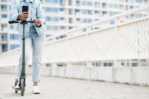スマートフォンを手に電動スクーターの上に立っているジーンズの若い女性のトリミング画像