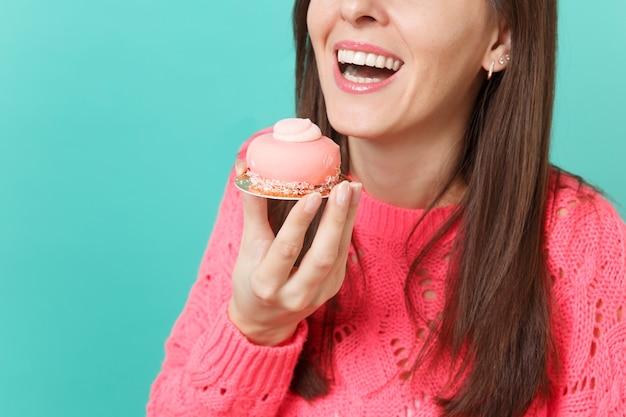 Обрезанное изображение молодой женщины в вязаном розовом свитере, держащей в руке торт, изолированном на синем фоне бирюзовой стены, студийный портрет. люди искренние эмоции, концепция образа жизни. копируйте пространство для копирования.