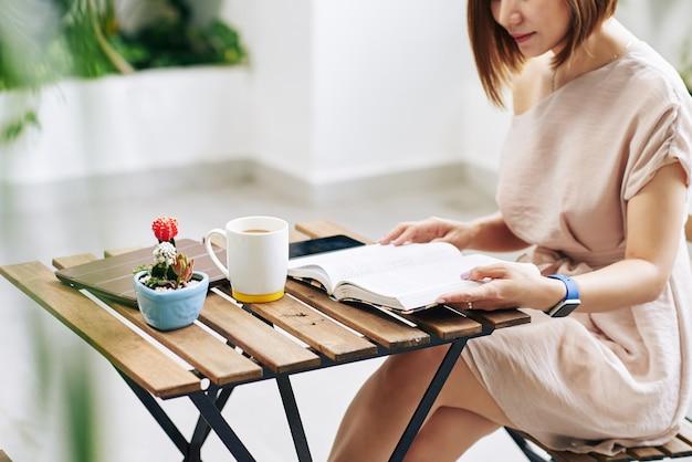 Обрезанное изображение молодой женщины, читающей книгу и пьющей утренний кофе в кафе